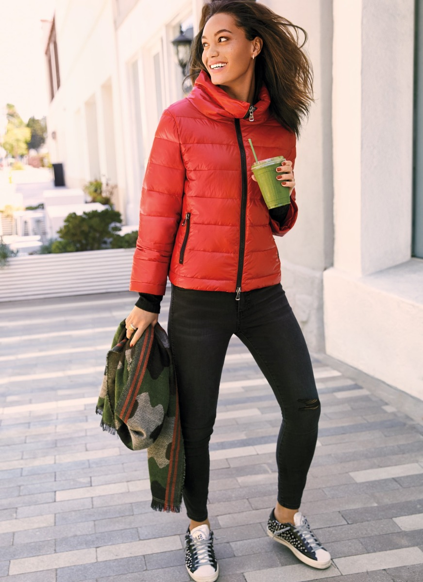 Woman wearing a red puffer jacket and black jeans with sneakers
