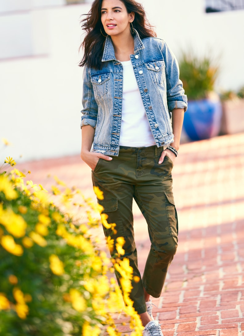 Woman with hands in her pocket wearing a denim jacket and camo pants