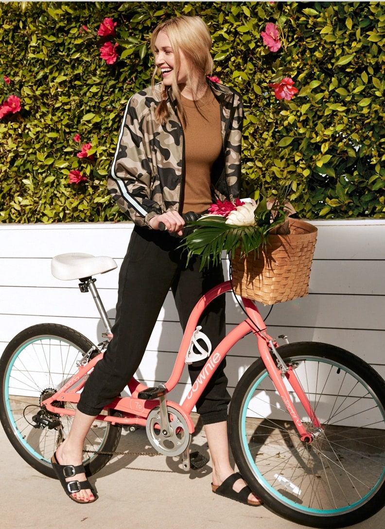 Woman on bike wearing camo jacket and joggers