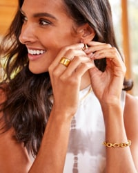 woman wearing an assortment of gold jewelry – shop jewelry