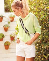 woman in neon yellow hoodie with white cutoffs – shop best sellers