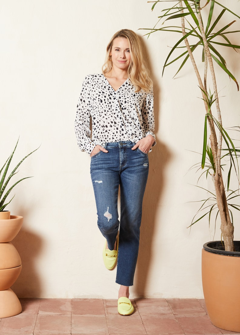 woman leaning against wall wearing spotted blouse, jeans and neon mules