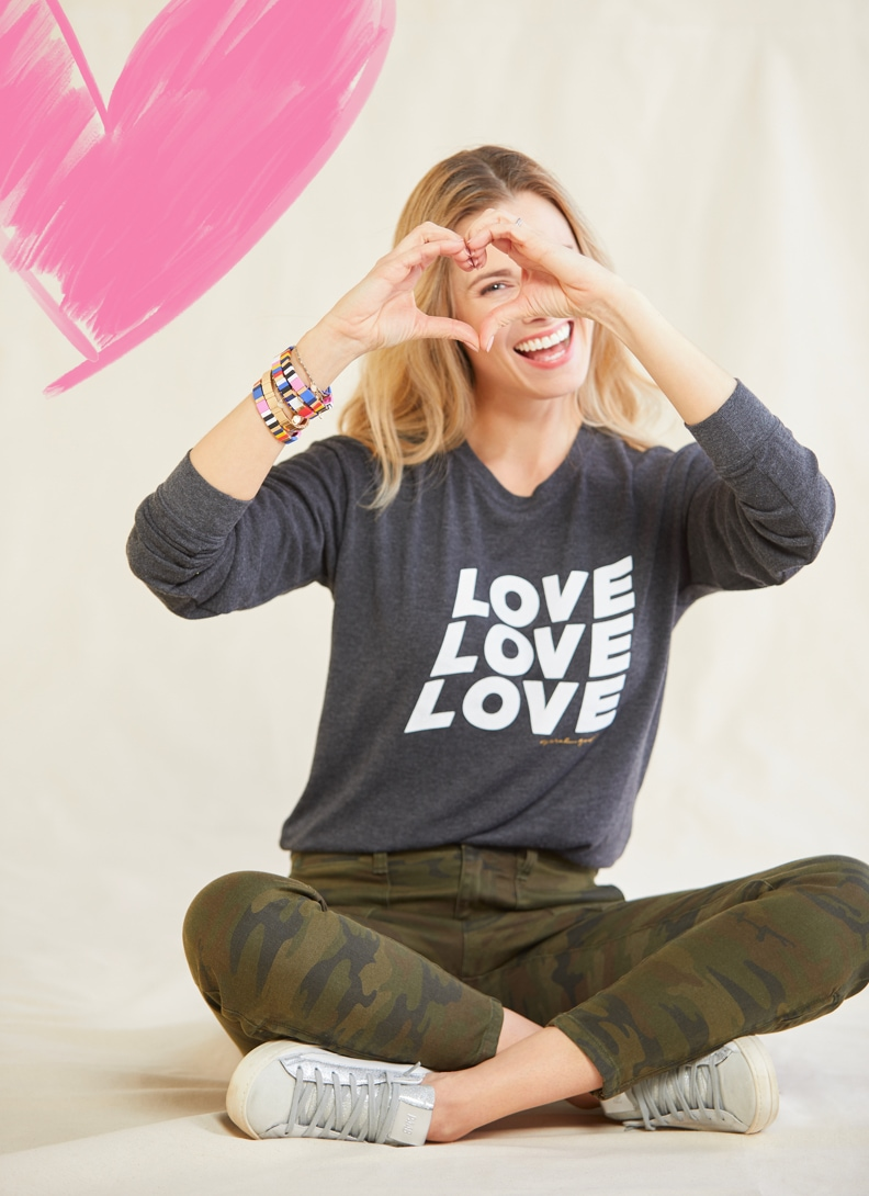 woman wearing love sweatshirt and making a heart with hands