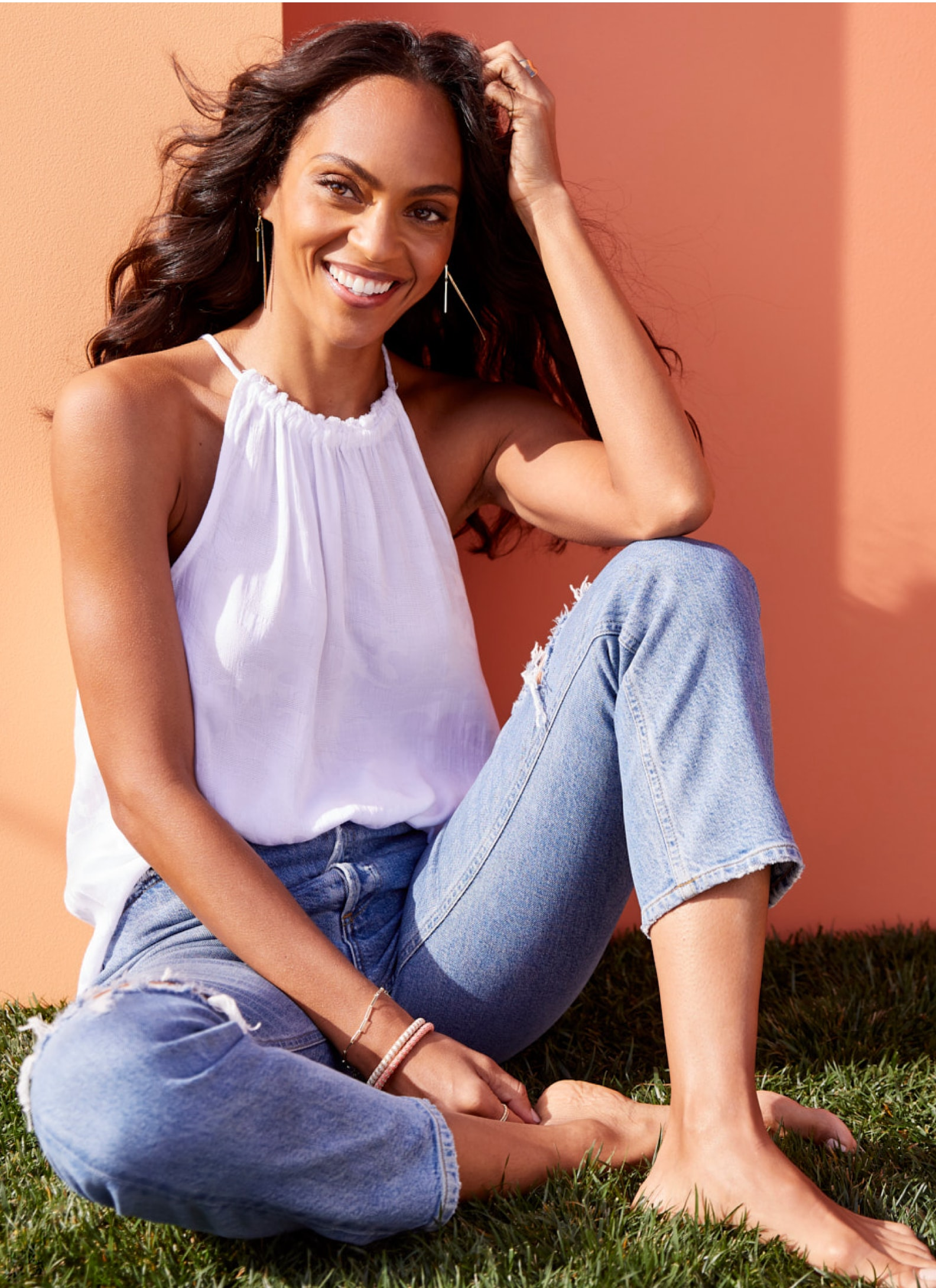 Woman wearing white tank and jeans