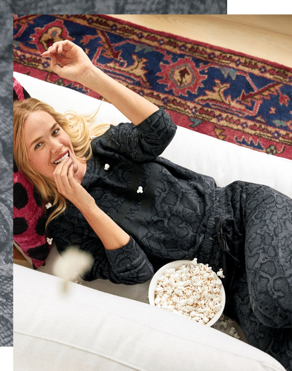 Woman sitting on couch eating popcorn in a track suit