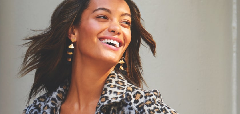 woman wearing gold statement earrings with animal print coat