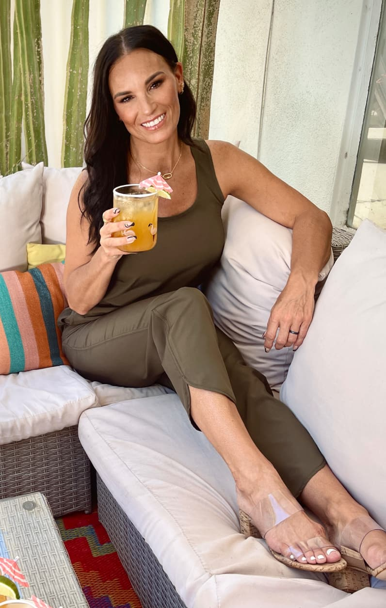 Woman wearing green jumpsuit sitting on couch