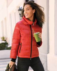 woman in red jacket walking with drink
