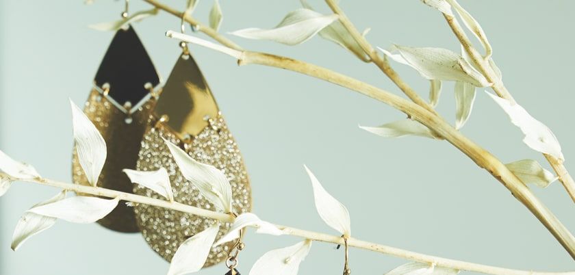 a pair of gold statement earrings hanging on a flowered branch