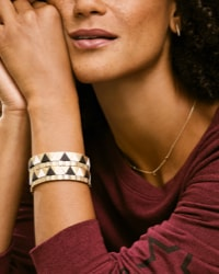 close-up of woman wearing a stack of colorful bracelets