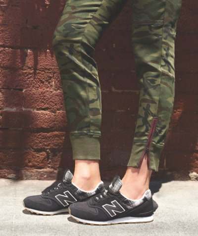 Camo utility pants with zipper along ankle and black New Balance sneakers