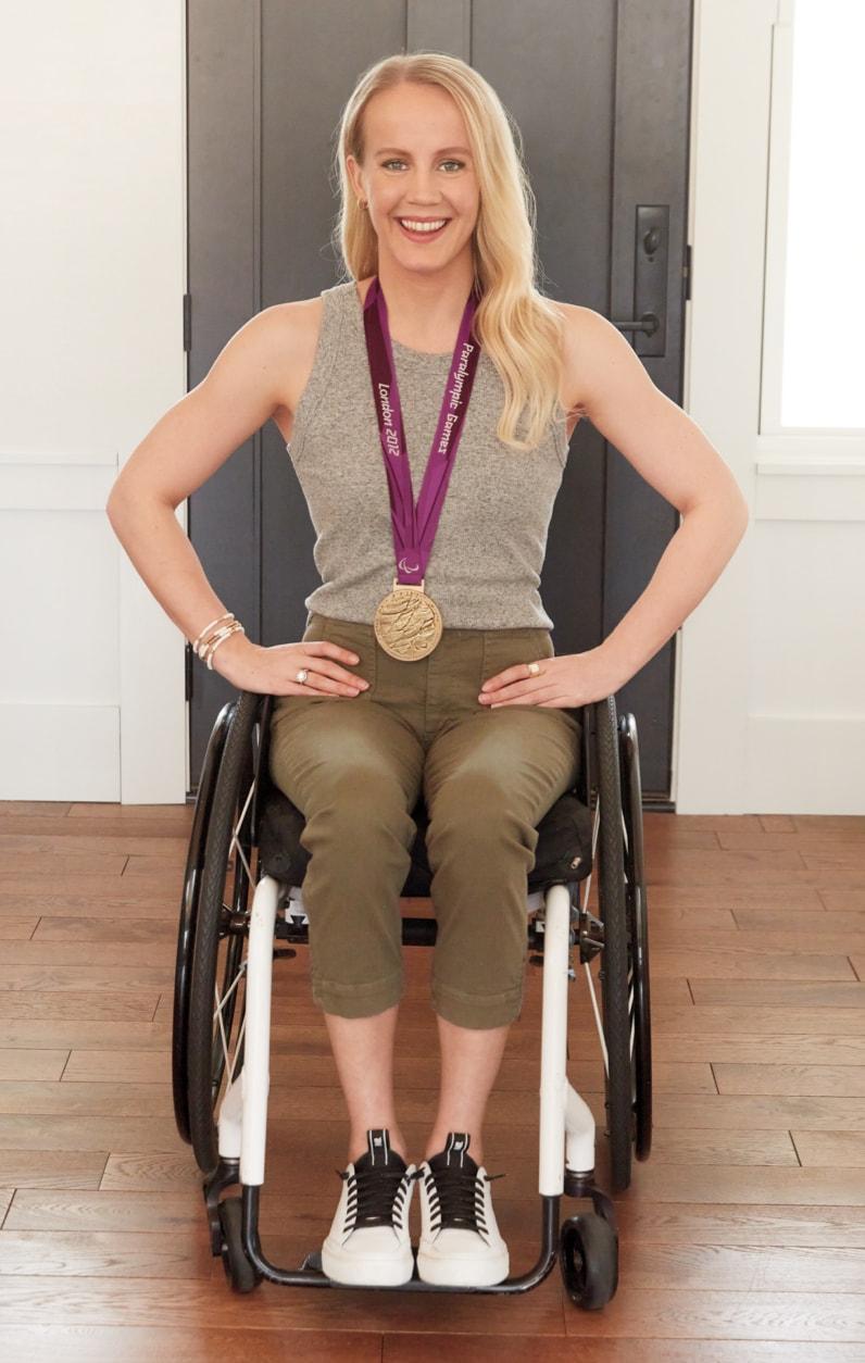Mallory wearing a gray tank, khaki pants and a Paralympic medal