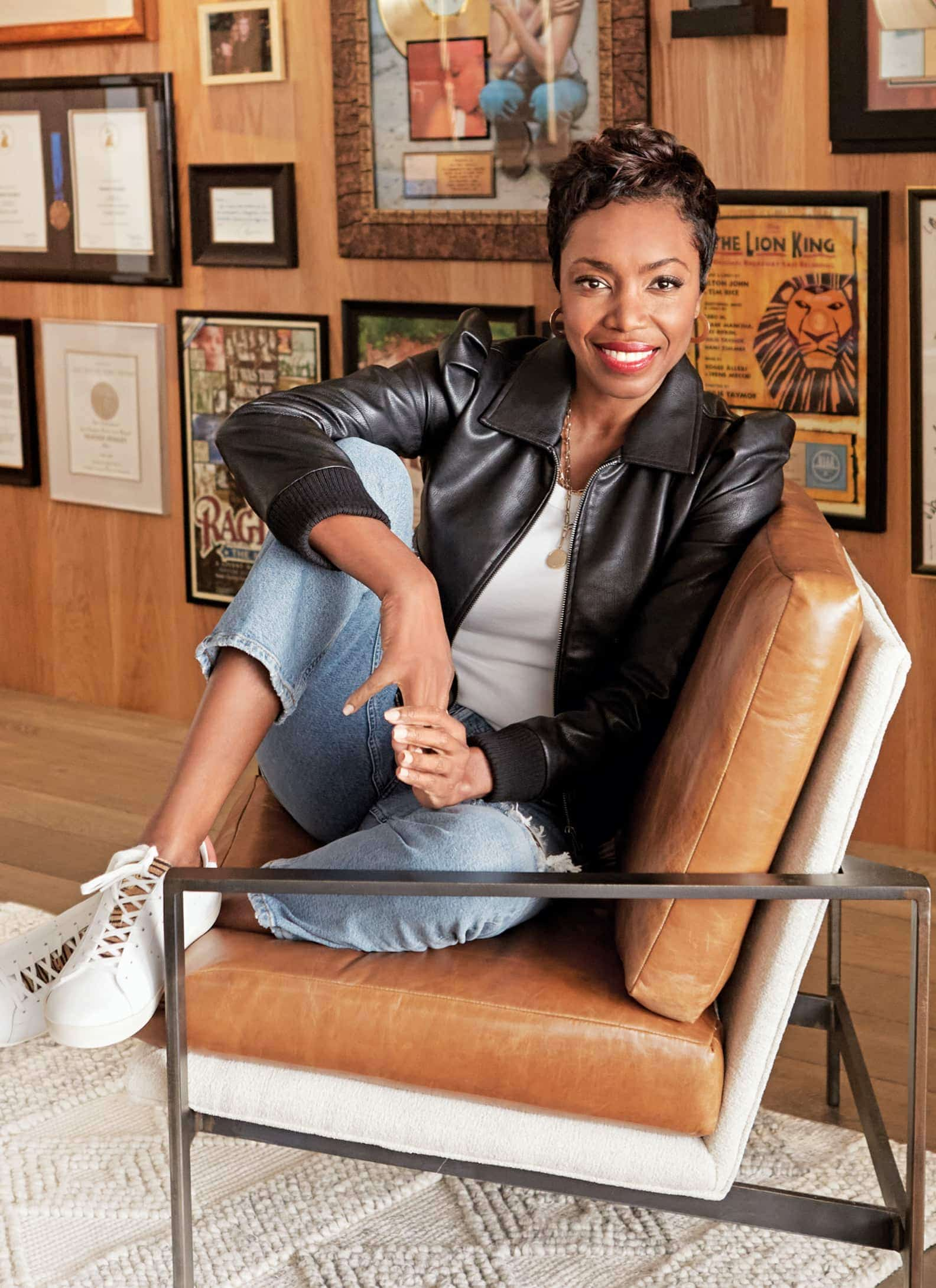 Woman wearing leather jacket, white tank, jeans and sneakers