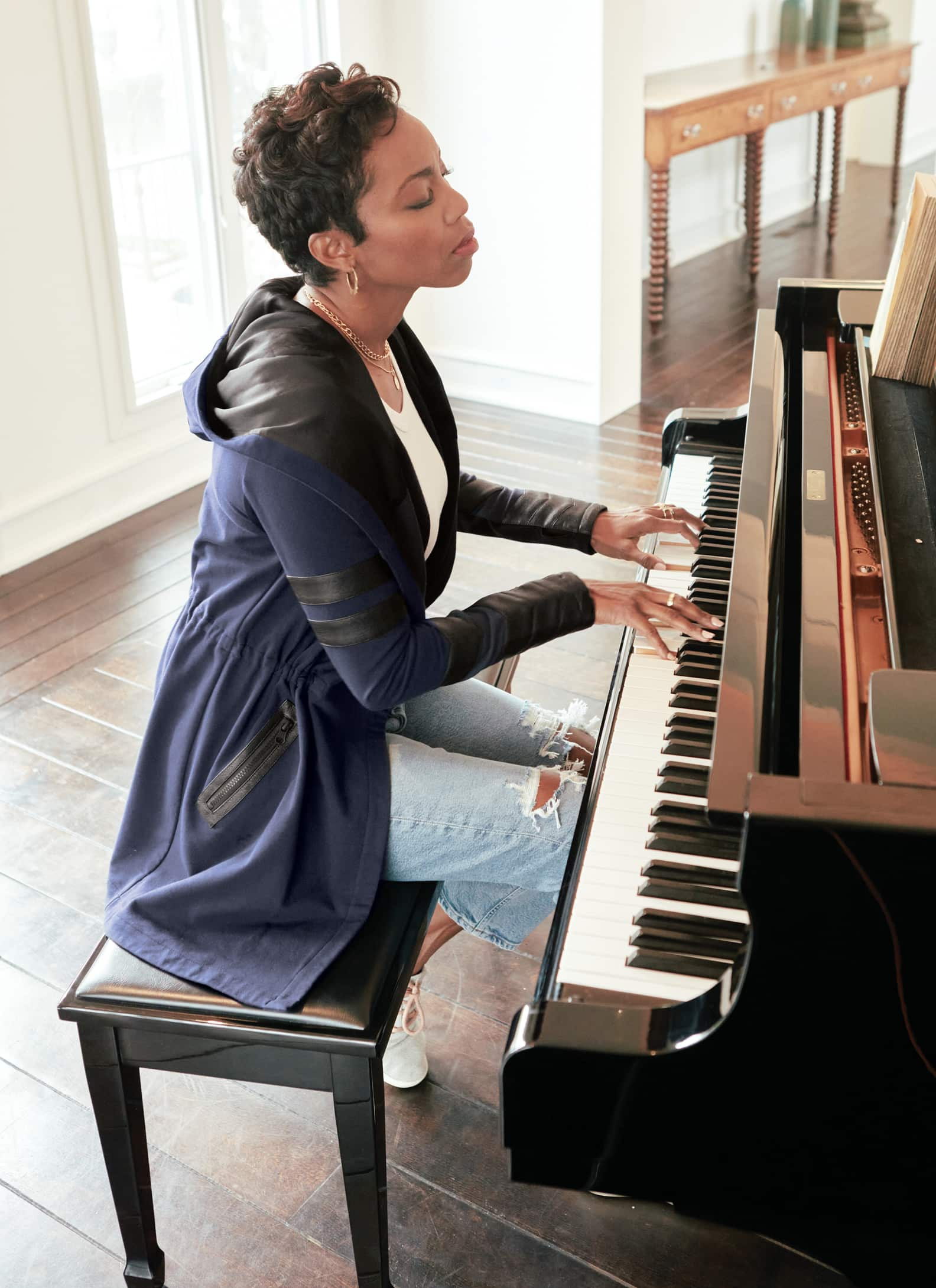 Woman at piano wearing jacket and jeans