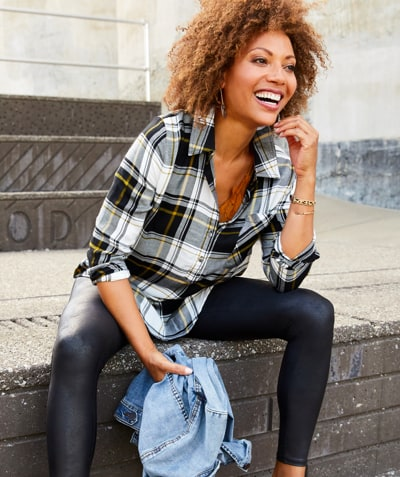woman in black white and yellow plaid button down with spanx holding jean jacket