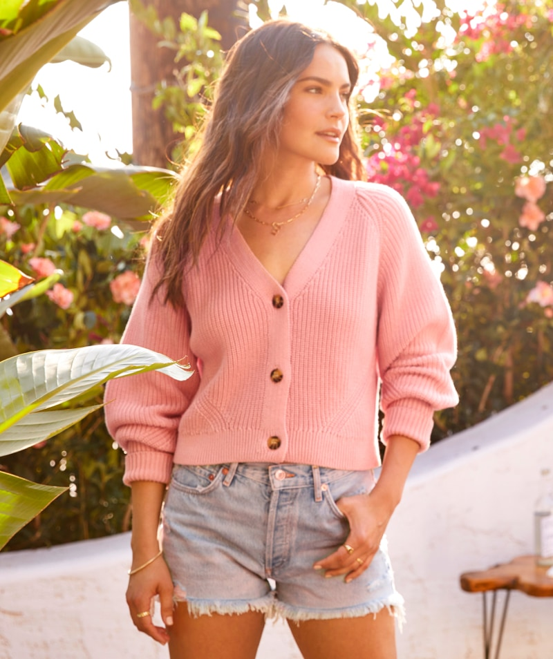 woman in pink sweater cardigan and cutoffs.