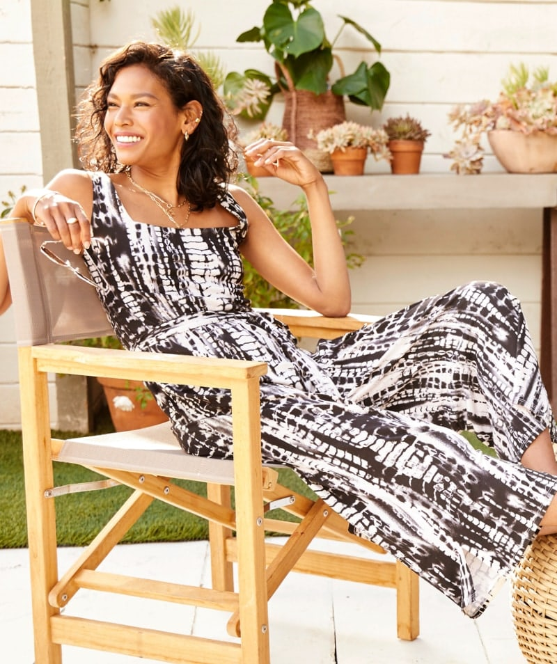 woman relaxing outside in black and white tie-dye print jumpsuit.
