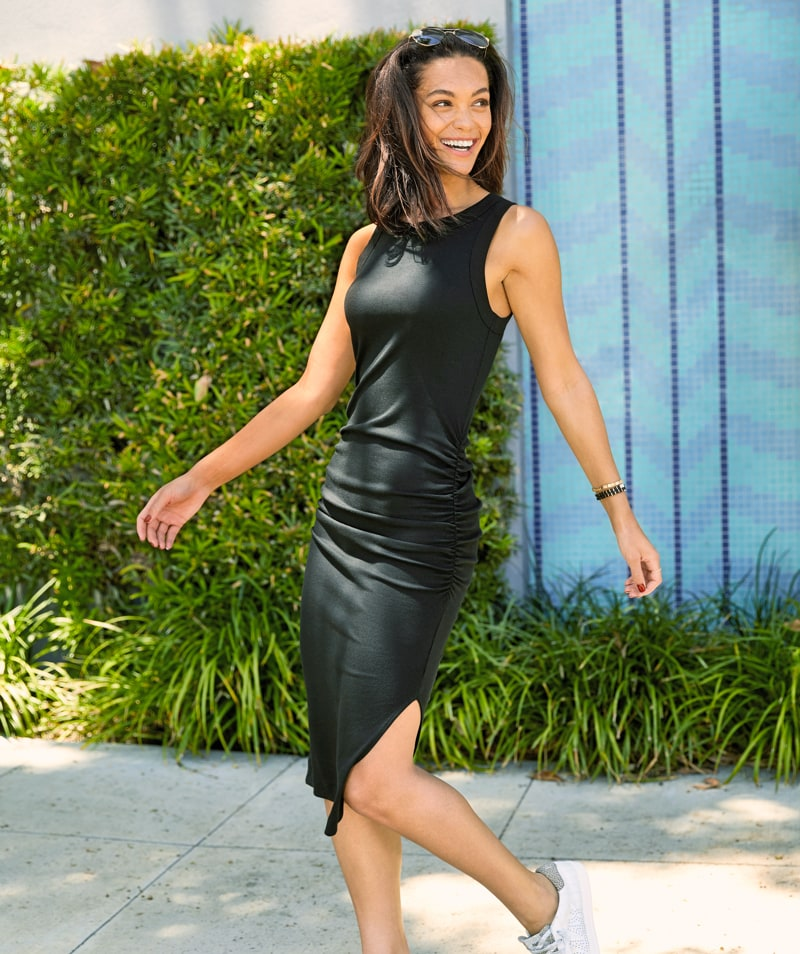 woman walking outside wearing a long fitted black dress and sneakers - shop dresses