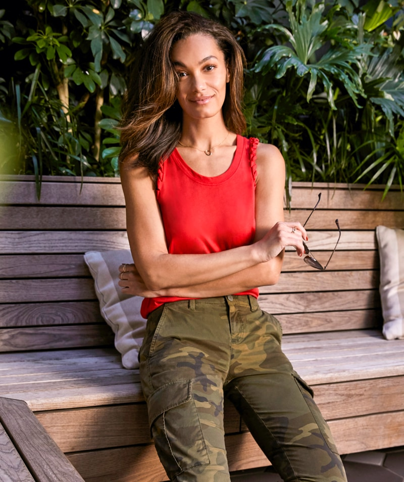 Woman in bright red-orange tank with braided sleeve details and camo utility pants - shop new arrivals