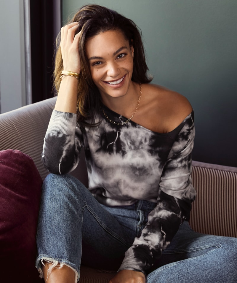 woman in black and white tie-dye off the shoulder top and jeans - shop new arrivals.