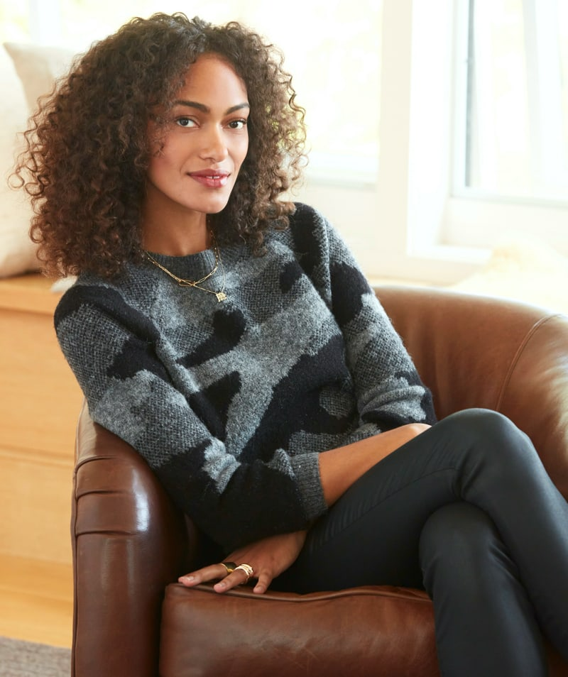 woman cozied up at home in black and grey abstract camo sweater and black pants.