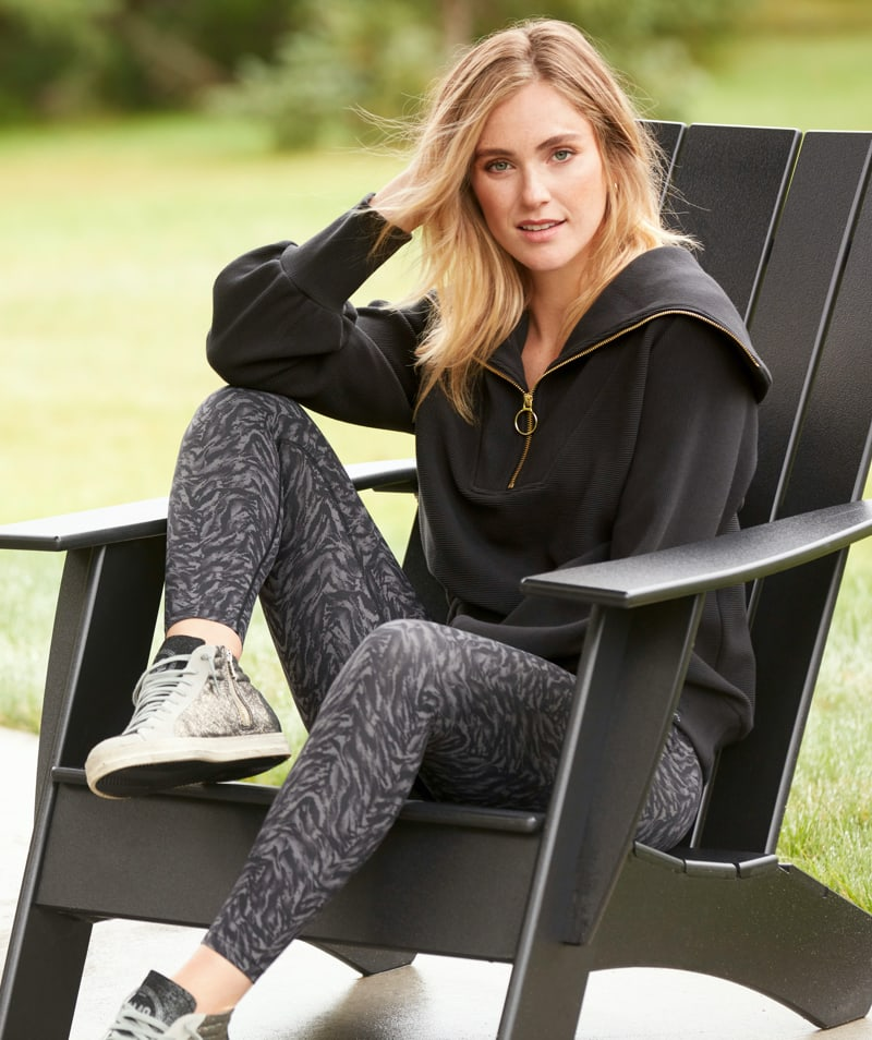 Woman relaxing outside in black tunic sweatshirt with grey and black animal print leggings.