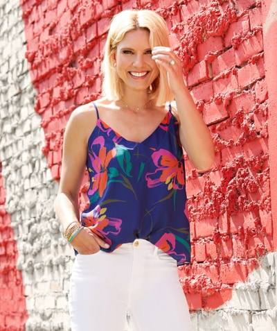 woman outside on a sunny day wearing a colorful cami tank and white pants