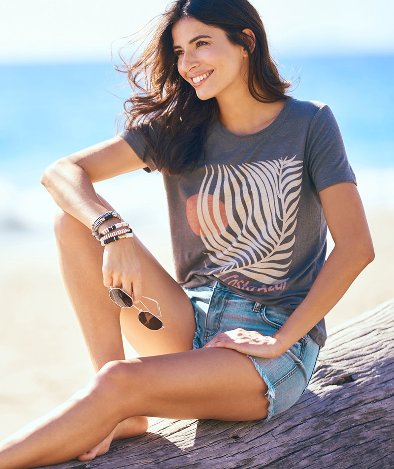 smiling woman in a palm print graphic tee and cutoffs sitting at the beach – shop tops