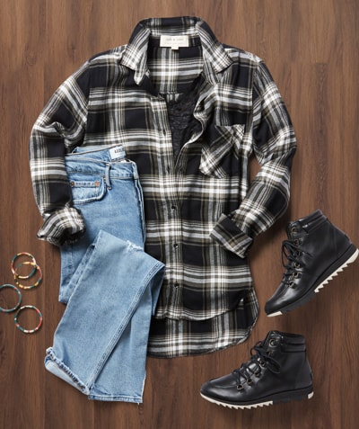 Laydown studio shot of a black and white plaid button-down, light-wash denim and Sorels