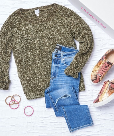 Green chenille sweater with distressed denim and sneakers laying next to a Trendsend box