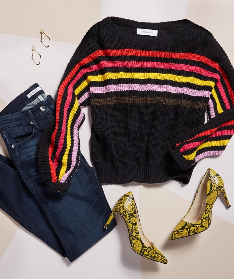 studio laydown of black sweater with warm colored stripes across the chest, dark wash jeans, yellow snakeskin heels - shop new arrivals