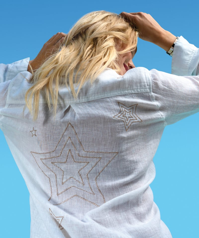 lifestyle shot of a woman in a white graphic button-down with a blue sky - stop tops