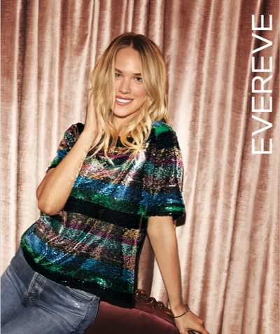 Evereve's holiday catalog cover – woman in colorful sequins top with blue jeans - shop the catalog