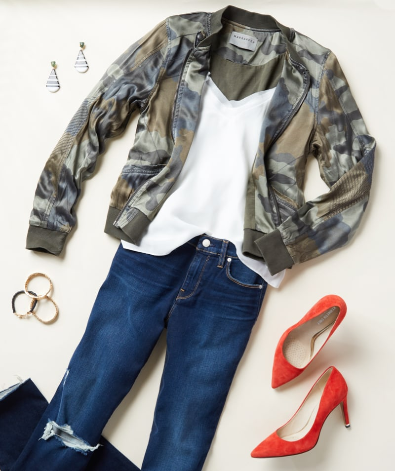 Laydown studio shot of a camo jacket with white top, denim and red heels - shop new arrivals