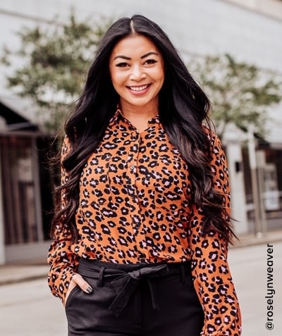 Woman in orange, black and pink animal print blouse with black pants - shop sanctuary