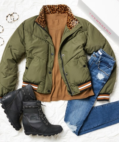 Studio laydown shot of green and animal print puffer jacket, black Sorel boots, blue jeans and Trendsend box - Shop Trendsend