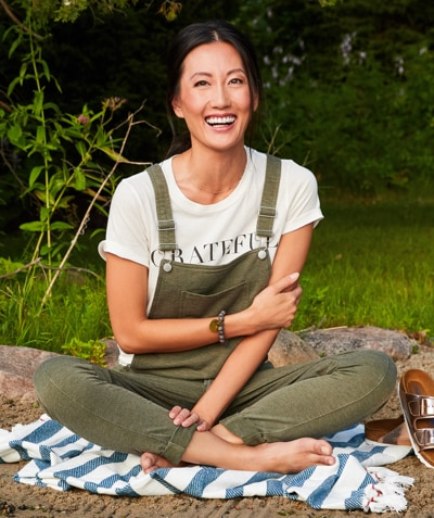 woman in graphic tee with olive green overalls