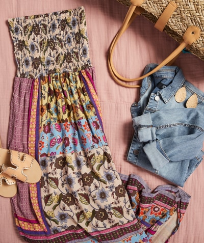 Studio laydown of brightly colored maxi dress, jean jacket, shoes, jewelry and beach bag