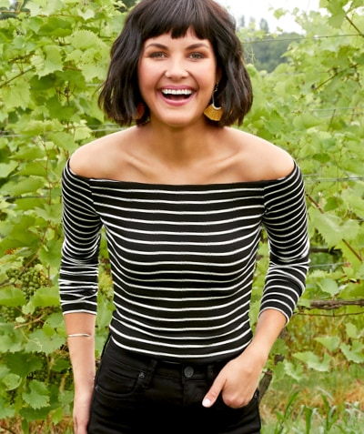 woman in a black and white stripe off the shoulder top with black jeans